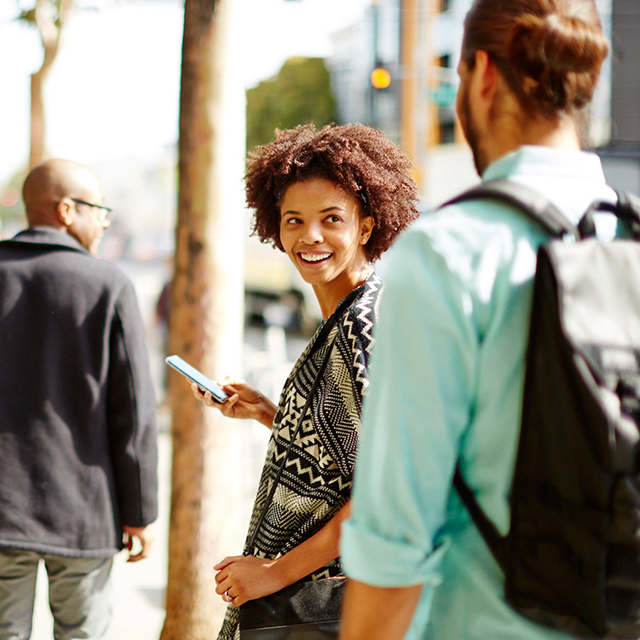 Woman smiling at a person behind her while holding a mobile phone